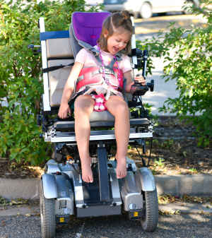 A young girl laughs and looks at her hand around the joystick as she sits in a motorized wheelchair for the first time.
