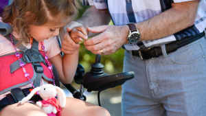 A male occupational therapist takes the hand of a young girl and helps her grab the joystick of a motorized wheelchair. A stuffed pink bunny sits on her lap.