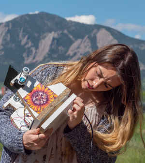 A female college student examines in her hands a solar-powered machine she and her classmates built. On the front of the contraption, which has gears and a mirror, is taped a printout of a cat wearing a sunflower costume. The flatirons are in the background.