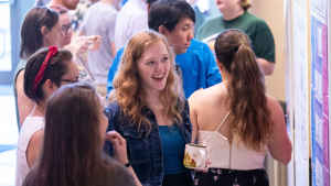 Willow Reed exclaims excitedly with her mouth open in the middle of a crowded student research expo while listening to a female college student explain her work.