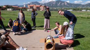 Clusters of college students stand outside on the CU Boulder East campus working together to build different projects. One group is working on a tube that will funnel sunlight. In the forefront a female student with a large leg tattoo checks her phone.