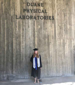 A young woman stands in her graduation regalia in front of a building that is named Duane Physical Laboratories on the CU Boulder campus.