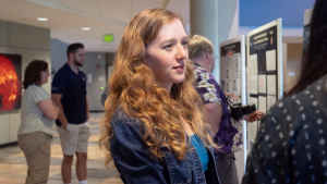 A young woman with long wavy red hair listens intently to a female college student explain her research in a crowded room. They are at an expo where college students share posters about the research they worked on all summer.