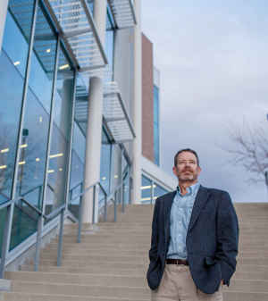 """Professor Charles """"Chip"""" Benight walks down the stairs of the Lane Center on the University of Colorado Colorado Springs campus."""