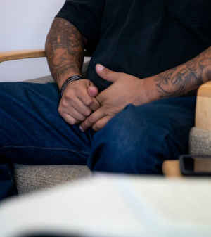 A man's hands clasp tightly together, the arms heavily tattoed, as he sits in a chair
