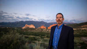 """Professor Charles """"Chip"""" Benight stands facing the sunrise in Garden of the Gods park in Colorado Springs"""