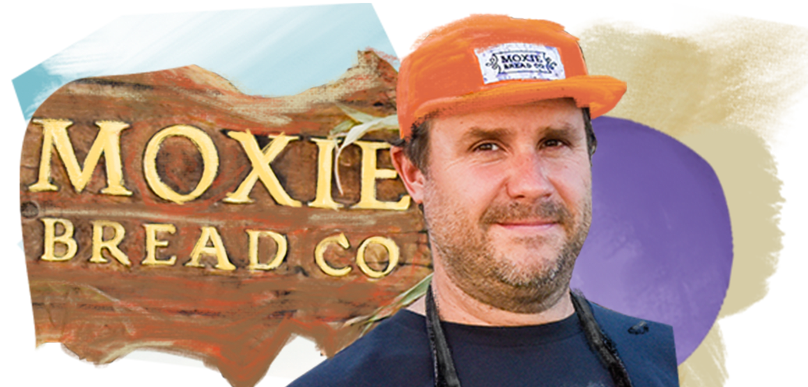 A man with a beard is wearing a T-shirt and an apron covered with flour. He is standing in front of a sign that says Moxie Bread Co.