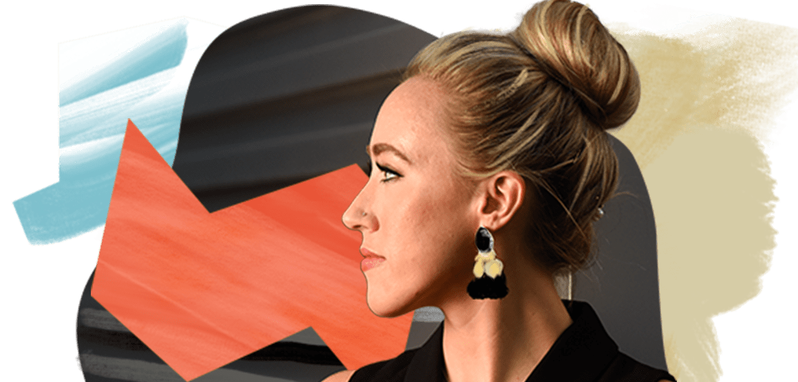 A woman in black who has her blonde hair in a top knot and is wearing dangly earrings looks to the side.
