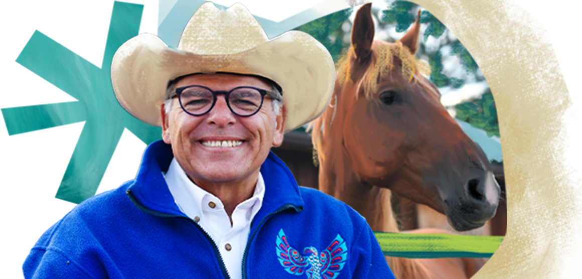 A man smiles broadly while wearig a cowboy hat, eyeglasses, and a bright blue fleece with a Native American bird symbol on it. The background is an artistic design with a brown horse depicted and colorful shapes