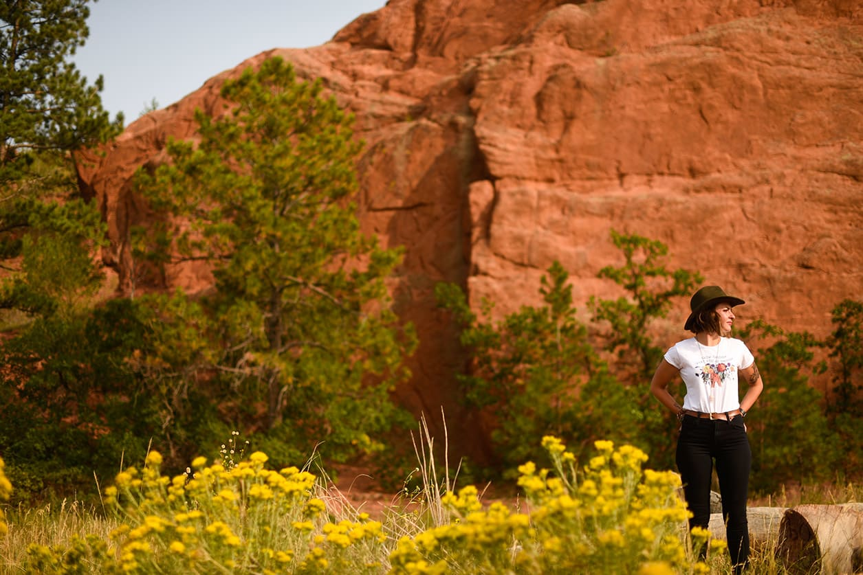 A woman is standing outside near a bluff in southern Colorado. She is wearing a hat, white shirt and black jeans.
