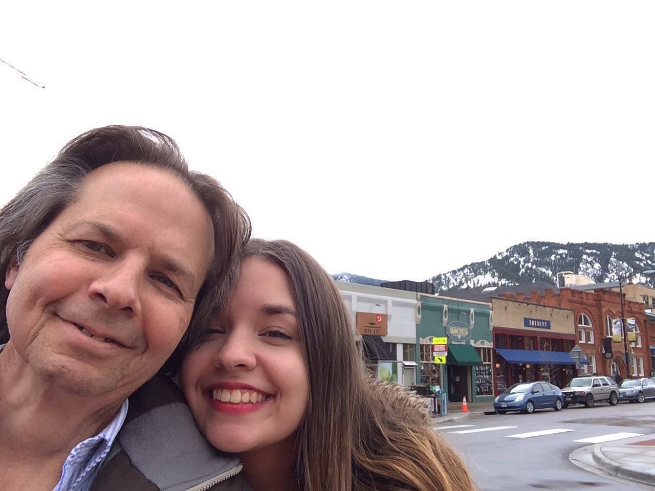 A young woman and her father stand for a selfie outside on Pearl Street in Boulder, Colorado. Snowy mountains are seen in the background.