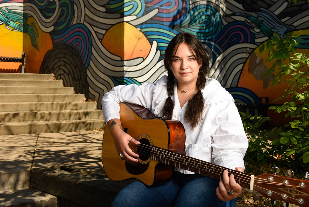 A young woman sits in front of a mural with her guitar.