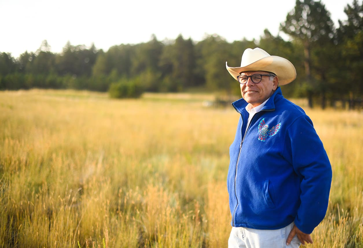 A man wears a blue fleece with a Native American bird symbol and a white cowboy hat while looking across his ranch.