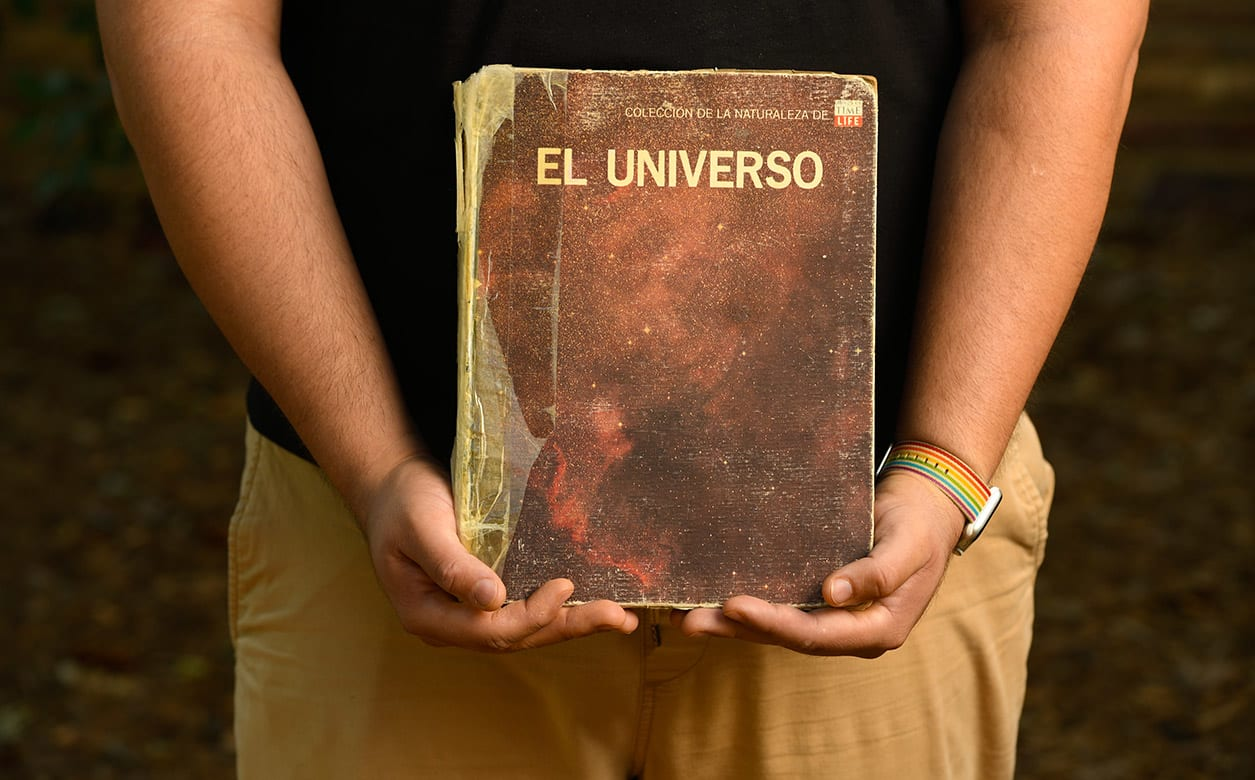 "A close up of a man's arms and hands holding a worn book titled ""El Universio."""