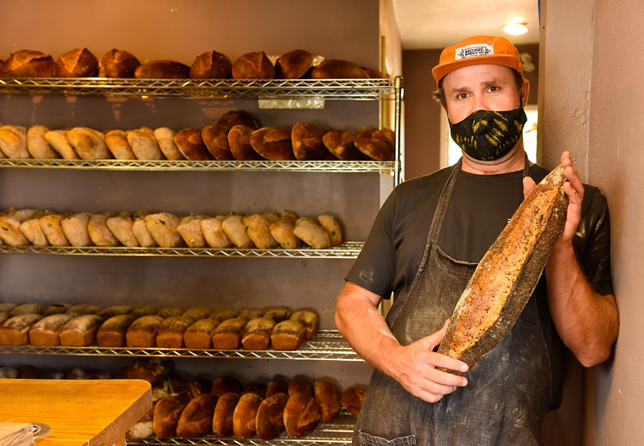This is a photo of Andy Clark who is holding a loaf of bread in his bakery with bread loafs on racks behind him.