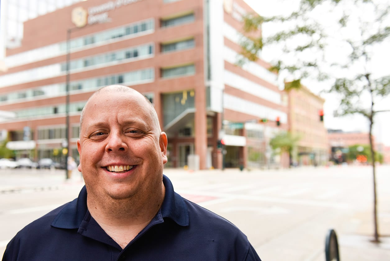A man poses in downtown Denver and smiles brightly at you.