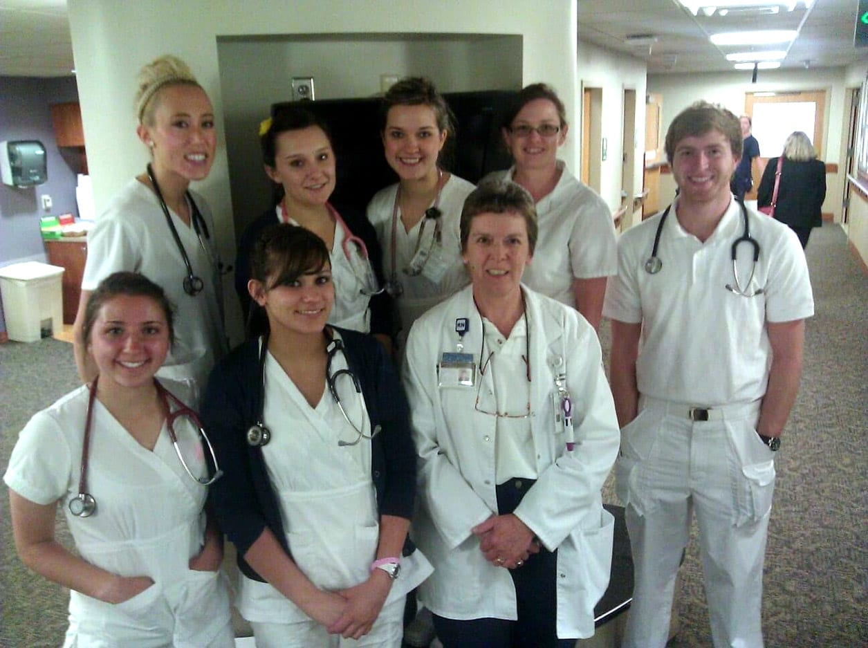 A group of nursing students stand together and smile for the camera.