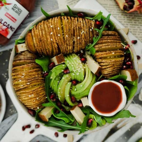 Image ofHasselback-Kartoffeln auf Rucolasalat mit Avocado, Granatapfel und veganem Himbeerdressing Vulcano