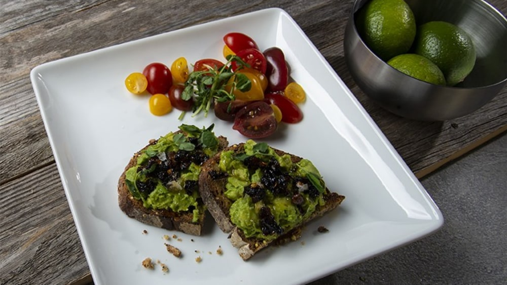 Square white plate with avocado toast topped with oo'mämē Chile Crisp and heirloom cherry tomatoes #avocadotoast