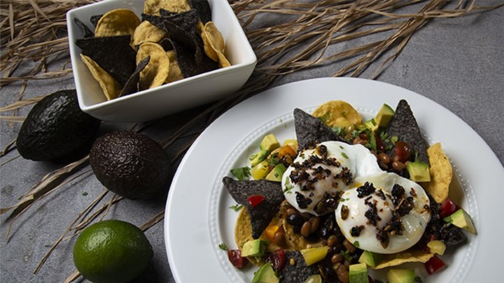 White round plate with chips, poached eggs, topped with Mexican oo'mämē Chile Crisp, avocado and tomatoes #huevos #myoomame