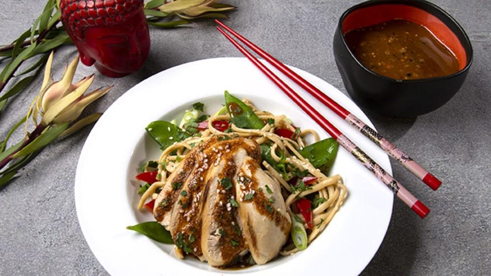 white bowl with noodles, chicken, snow peas, oo'mämē peanut sauce, with chopsticks and flower #coldsesamenoodles