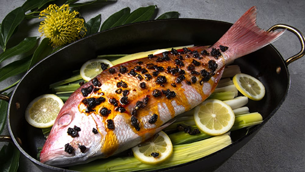 Whole red snapper with oo'mämē marinade in roasting pan on leeks and lemon slices. #myoomame