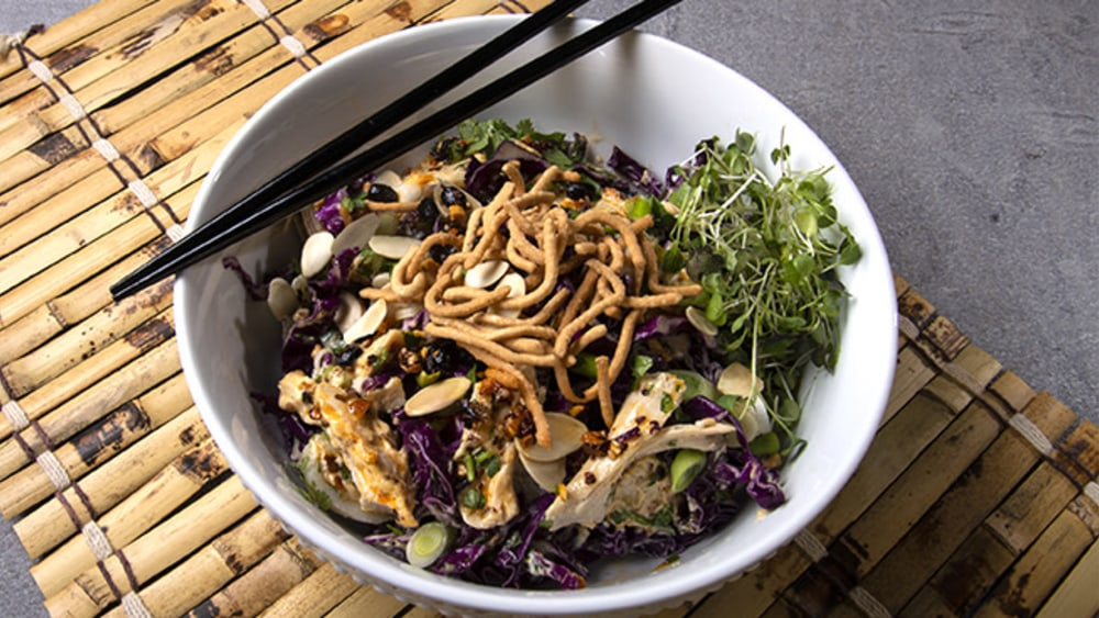 White bowl with Chinese chicken salad, topped with chow mein noodles on bamboo mat with chopsticks #myoomame