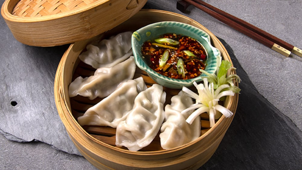 Bamboo steamer with steamed potstickers and bowl of dipping sauce with chopsticks #dumplings #myoomame