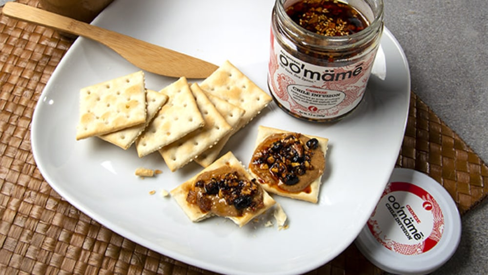 White plate on woven mat with a jar of Chinese oo'mämē chile crisp, saltines topped with peanut butter and oo'mämē #myoomame