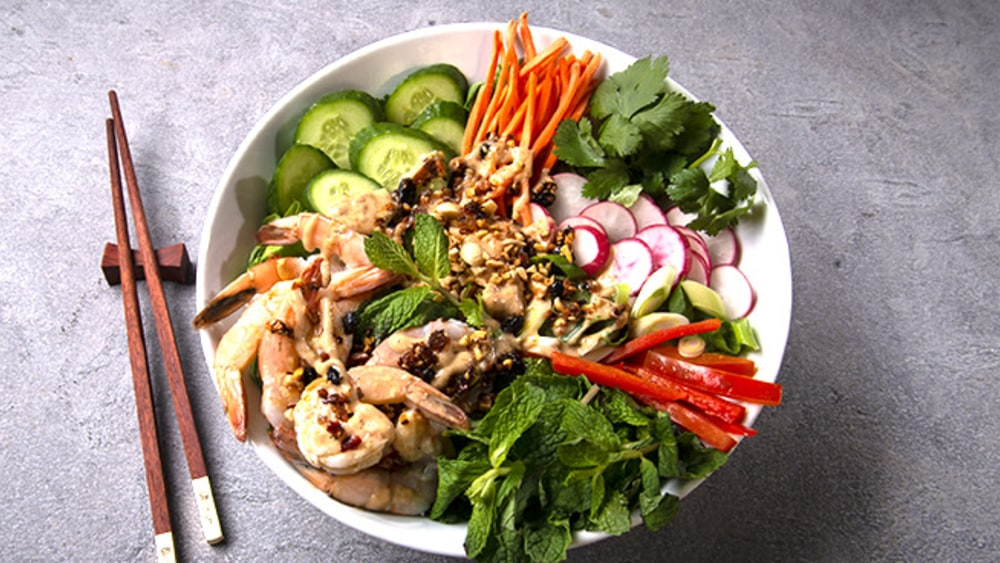 White shallow bowl with Chinese shrimp salad: Cucumbers, radishes, carrots, peppers, shrimp and herbs, topped with oo'mämē Chinese dressing #spicydressing #myoomame