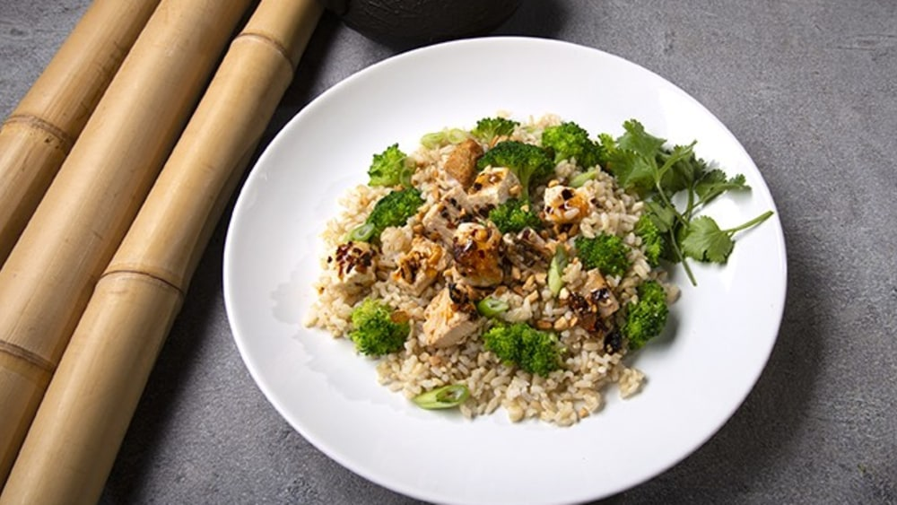 White plate with broccoli, tofu marinated in oo'mämē, and brown rice with cilantro. Bamboo reeds. #veganrecipe #myoomame