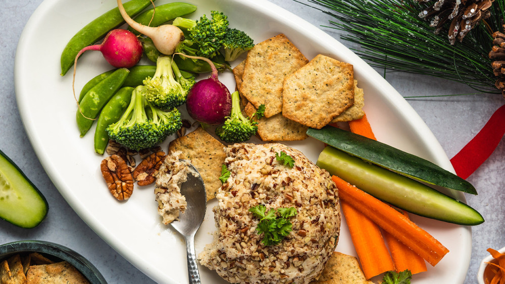 vegan cheese ball on a white platter with a silver spoon scooping out some of the cheese. Also on the platter: chopped broccoli, radishes, carrot and cucumber sticks, snap peas, pecans, and crackers.