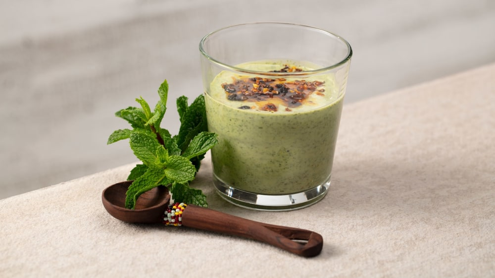 Glass of cilantro mint dressing with a wooden spoon and fresh mint