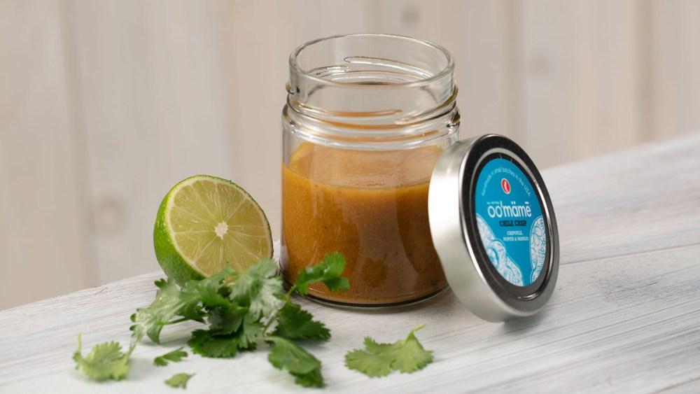 Jar of oo'mämē lemon vinaigrette with lime half and fresh cilantro
