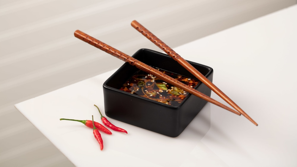 Square black dish with dumpling dipping sauce, chopsticks and red chile peppers