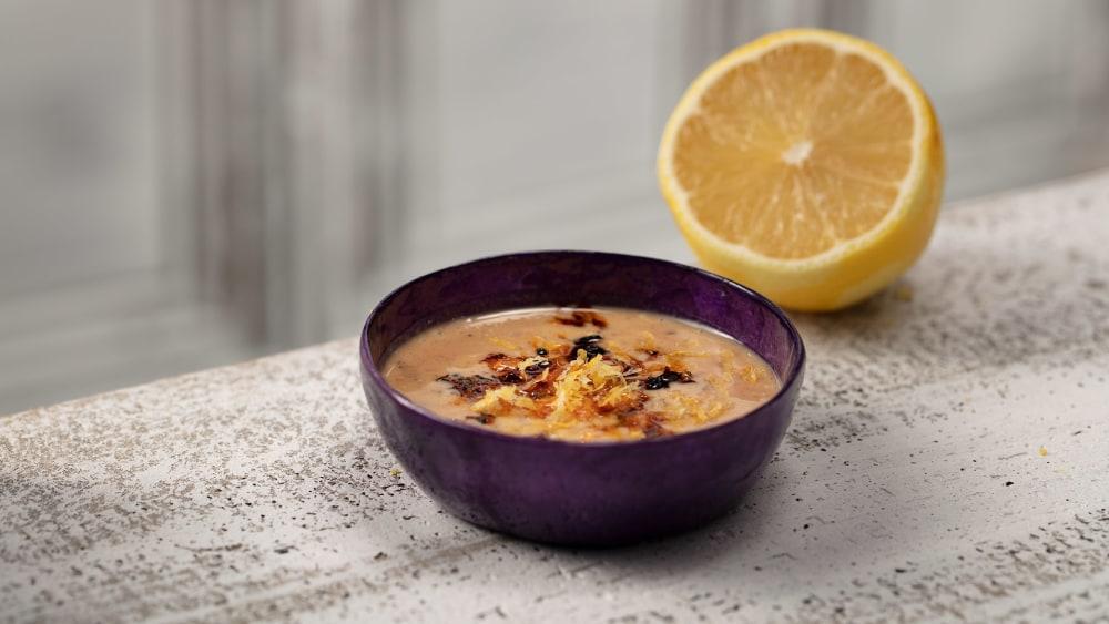 purple bowl with lemon tahini oo'mämē dressing and half a lemon