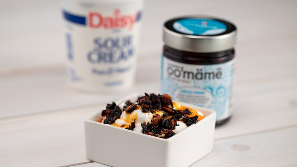 Square white dish with sour cream topped with Mexican oo'mämē, oo'mämē jar and container of sour cream