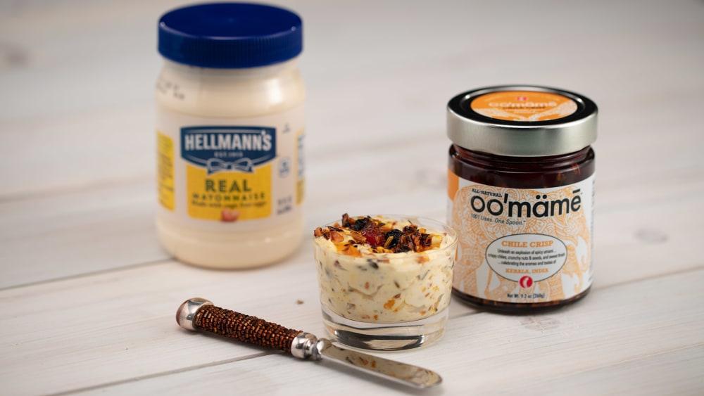 Glass dish with Indian oo'mämē mayo, small knife, jar of Indian oo'mämē Chile Crisp and jar of mayonnaise.