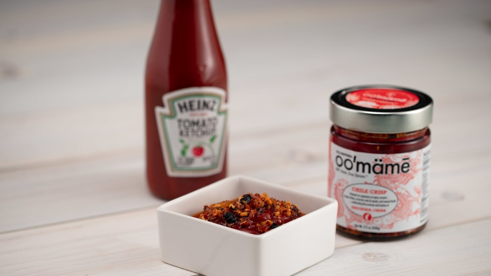 Square white dish with ketchup and oo'mämē, jar of oo'mämē Chinese Chile Crisp and bottle of ketchup