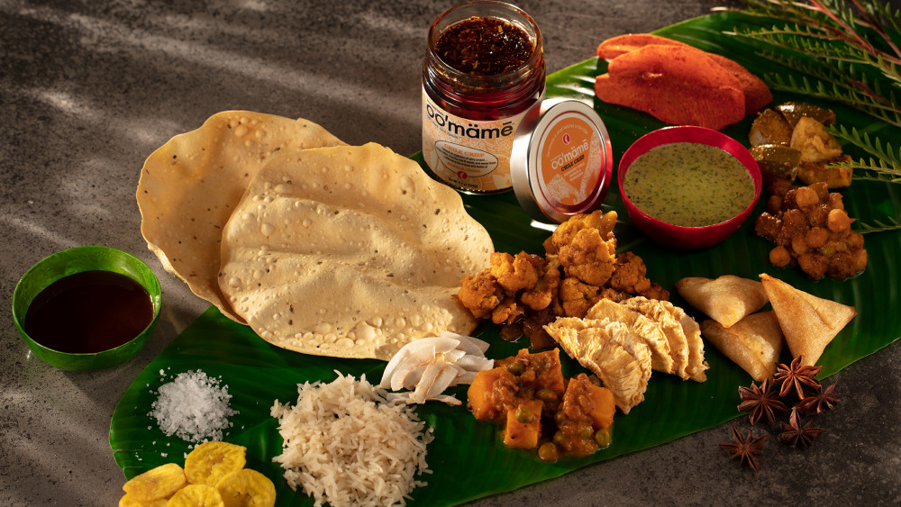 banana leaf covered with Indian vegetarian side dishes, pappadum, chutneys and a jar of oo'mämē Indian Chile Crisp