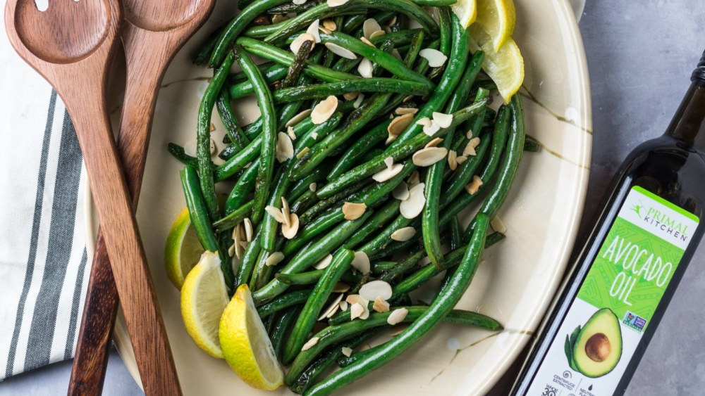 Sauteed green beans with sliced almonds and lemon wedges on a large white platter. Brown wooden spoons are resting on the plate. Primal Kitchen Avocado Oil is next to the plate.