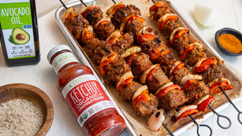 A bottle of ketchup lays next to a pan covered in parchment with four beef skewers on it, covered in peanut sauce, with red pepper and onion.