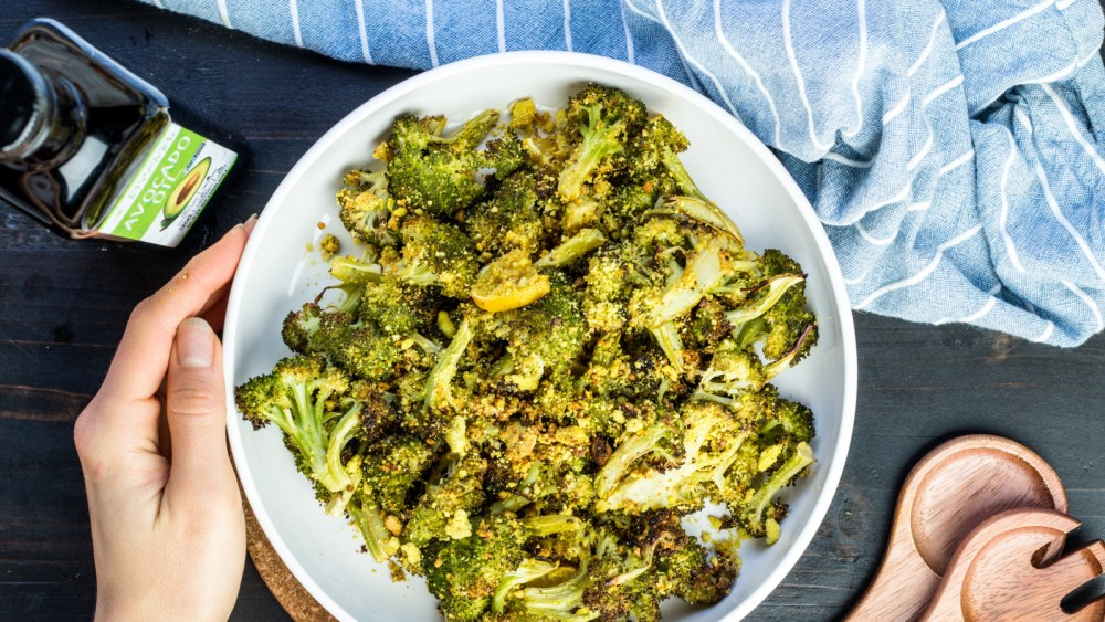 Hands cradling a big white bowl filled with roasted broccoli with cheese sauce. Next to the bowl are wooden spoons, Primal Kitchen Avocado Oil, and a blue napkin with white stripes.