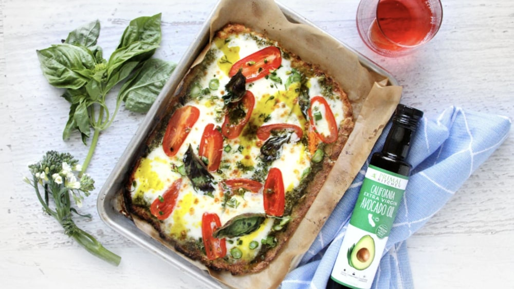 A bottle of extra virgin california avocado oil lays next to a pan with a pizza topped with melted mozzarella and green pesto. There are a few basil leaves and a blue tea towel nearby.
