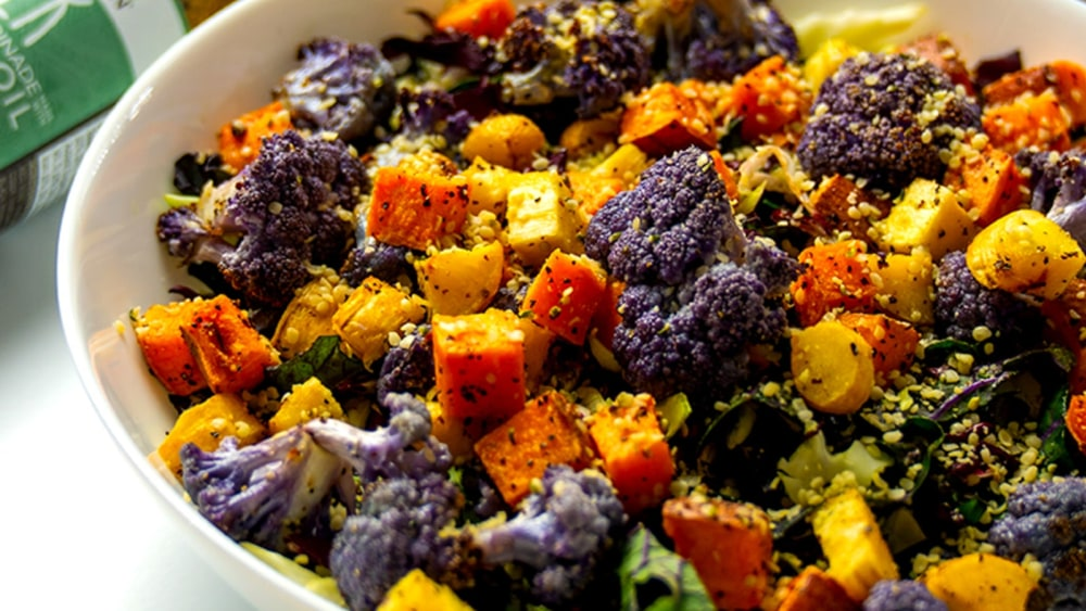 A dish of roasted vegetables with hemp seeds and kale slaw, with greek dressing in the background.