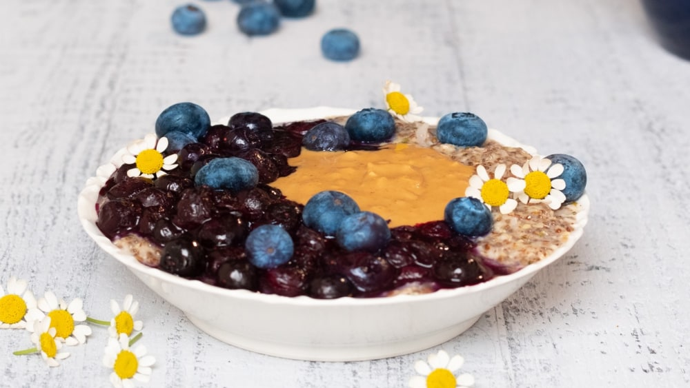 Noatmeal in a large white bowl topped with stewed blueberries, fresh blueberries, almond butter, and baby daisy flowers. Fresh blueberries and daisies scattered around the bowl.