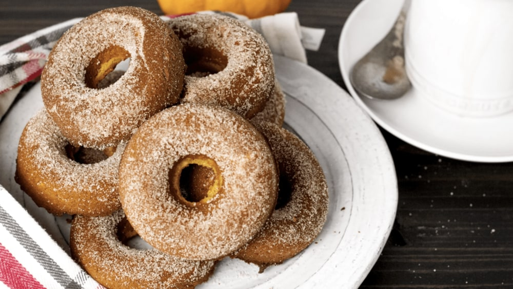 A white plate with a stack of pumpkin spice keto donuts with a mini pumpkin and coffee-coated spoon in the background.