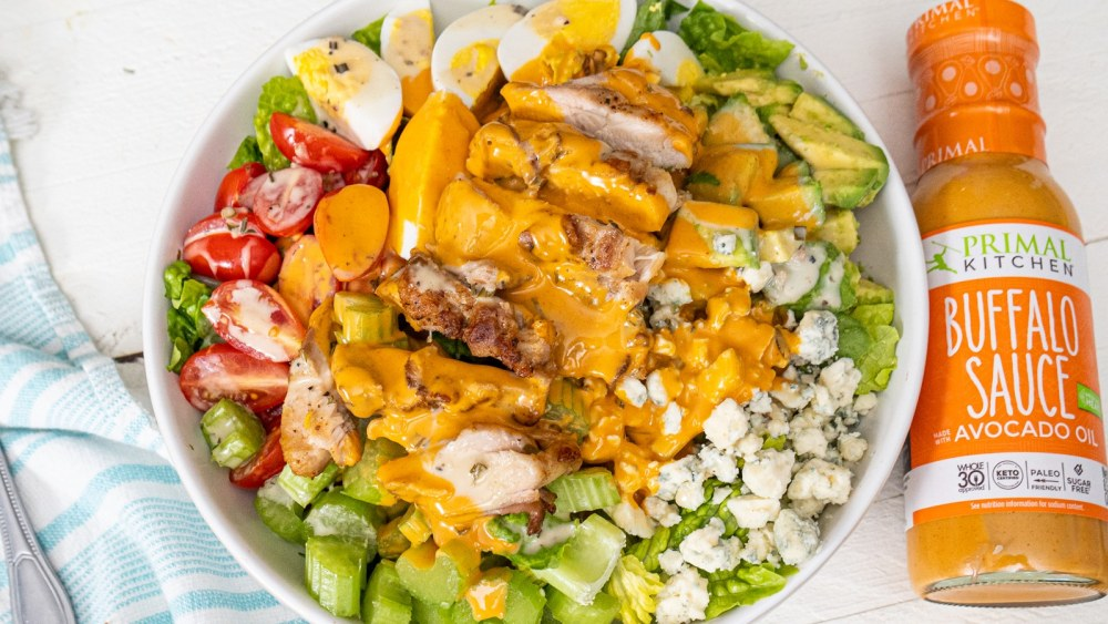 Chicken Cobb Salad with Buffalo Ranch Dressing in a large white bowl. Next to the white bowl is Primal Kitchen Buffalo Sauce and a white and blue napkin.