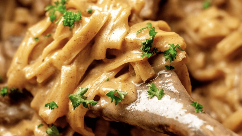 Beef Stroganoff nodles topped with parsley are on a wooden spoon.