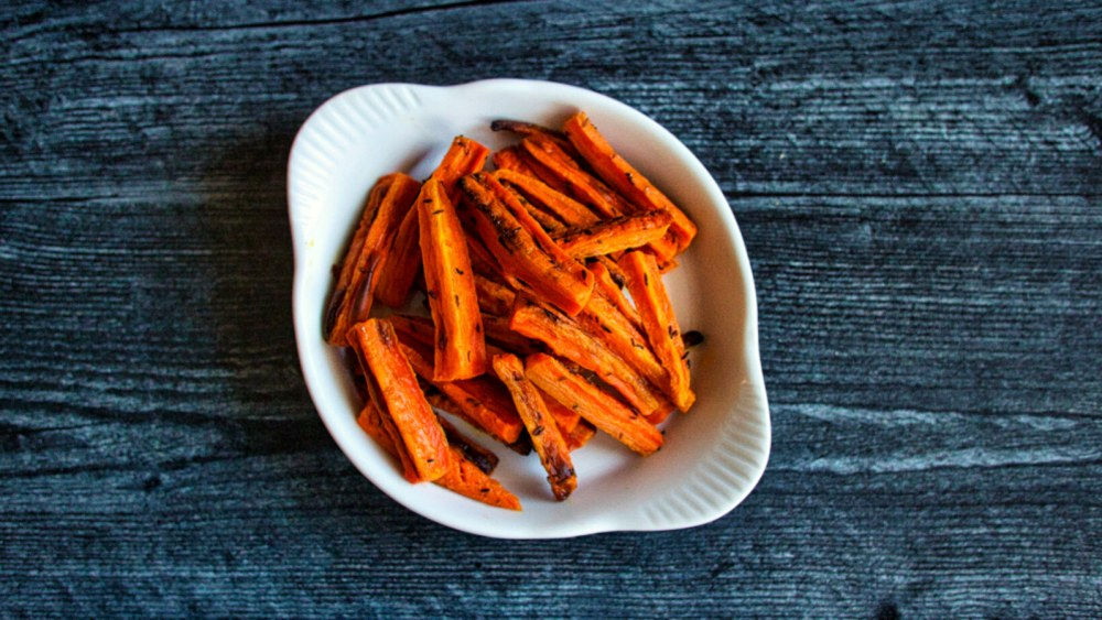 roasted black cumin carrots on a while plate